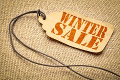 Winter sale price tag. Winter sale sign - red stencil text on a paper price tag against burlap canvas stock photography