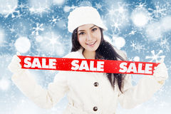 Winter sale with red banner on blue background. Portrait of fashionable woman showing banner of winter sale. isolated on white background Royalty Free Stock Image