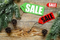Winter sale. Sale labels near spruce branches on wooden background top view copyspace Royalty Free Stock Images