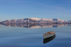 Winter Scape. With Snowy Mountains and a Boat on a Calm Lake Royalty Free Stock Photo