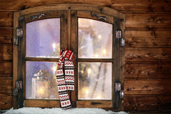 Winter scarf hanging in a Christmas window Royalty Free Stock Photos