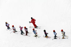 Winter scene. Kids learning to ski and their instructor royalty free stock photo