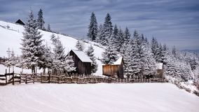 Winter scene in the Carpathian mountains , remote and harsh environment. With blizzard and wind and lenticular clouds ,old houses and traditional houses stock photography