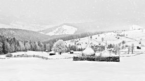 Winter scene in the Carpathian mountains , remote and harsh environment. With blizzard and wind and lenticular clouds ,old houses and traditional houses stock photos