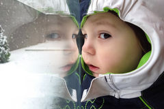 Winter scene with child looking out the window at. Snowflakes during snowfall dressed with winter clothes and hood Royalty Free Stock Photography