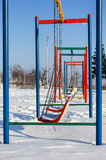 Winter scene with couple of swings in park Stock Photos