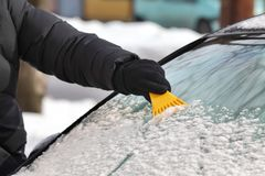 Winter scene, driver cleaning windshield of car. Driver cleaning snow from windshield of car using scraper closeup of hand and tool Stock Image