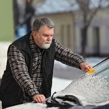 Winter scene, driver cleaning windshield of car. Driver cleaning snow from windshield of car using scraper, winter scene Royalty Free Stock Photography