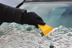 Winter scene, driver cleaning windshield of car Stock Photos