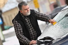 Winter scene, driver cleaning windshield of car Royalty Free Stock Photo
