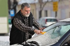 Winter scene, driver cleaning windshield og car Royalty Free Stock Photography