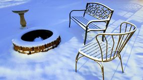 Winter Scene, Fire Pit, Birdbath, Metal Chairs in The Snow. Snow covered metal lawn chairs, concrete birdbath, outside Fire Pit Covered with Snow Royalty Free Stock Image