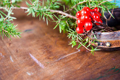 Winter scene with fresh green branches of pine, holly, juniper, cones, star, red berries barberry in natural wooden Royalty Free Stock Photos