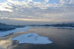 Winter scene. Ice on the river in the city, snowy banks with trees and houses, and cloudy sky. Siberia. Russia landscape royalty free stock photos