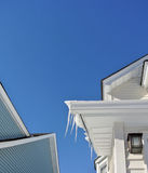Winter scene icicles on a bright clear blue sky  a New England roof Royalty Free Stock Photos