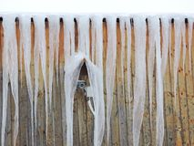 Winter scene - Icicles and control video camera on the roof of mountain house. Winter scene in the mountain. Icicles - hanging, tapering piece of ice formed by stock image
