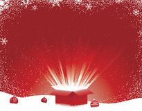 Winter Scene with Light Burst Gift Box. Gift box exploding open with rays of light on snowflake and snow dotted red background Stock Photos