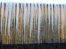 Winter detail - Icicles - formations of ice that descend from the roof of mountain house. Winter scene in the mountain. Icicles - hanging, tapering piece of ice stock images