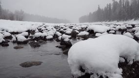 Winter Scene on Mountain River. During Heavy Snowfall stock footage