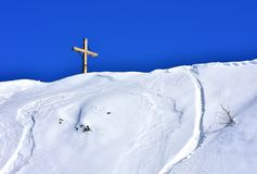 Winter Scene Mountains Blue White. Beautiful view of the wooden cross that stands in the top of a snowy hill. With clear blue sky for the background. Vogel royalty free stock image