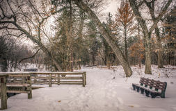 Winter scene at a park in Wisconsin with a vacant park bench. Winter scene in Wisconsin with snow covered vacant park bench and pier Royalty Free Stock Photos