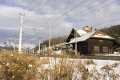 Winter scene of railroad station and mountains. Low angle view of passenger rail station with overhead electric power lines leading toward huge mountains in Stock Photography