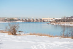 A winter scene of a river with a dam Royalty Free Stock Image