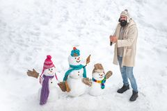 Winter scene with snowman on white snow background. Happy winter snowman family. Mother snow-woman, father snow-man and stock photos