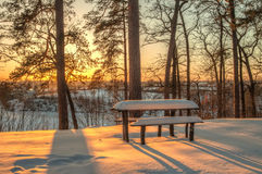 Winter scene, table, bench and trees in the snow on the sunset. Royalty Free Stock Images