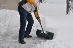 Winter scene - a tall Caucasian man shovels a driveway in a residential area in Ontario Canada Royalty Free Stock Images