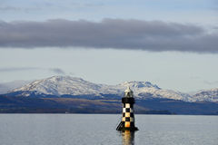 Winter scene. View of the  lighthouse known as the Port Glasgow Beacon or Perch Light situated on the  river Clyde at Port Glasgow, Scotland. The hilltops on the Stock Images