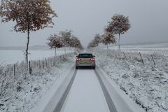 Winter scene of a VW Golf MK7 variant/estate on a narrow tree lined road between fields. Volkswagen Golf MK7 variant/estate in tungsten silver metallic with Royalty Free Stock Images