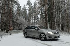 Winter scene of VW Golf MK7 estate variant in snowy pine tree forest. Volkswagen Golf MK7 variant/estate in tungsten silver metallic with Team Dynamics PR3 alloy stock photo