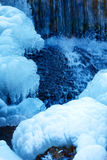 Winter scene with water falling from icy rocks. Blue color. Royalty Free Stock Photography