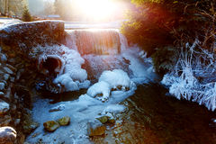 Winter scene with water falling from icy rocks and sun light. Stock Images