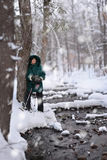 Winter scene. Woman with  snowshoes leaning on tree by a stream Stock Image