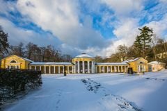 Winter scene of yellow building of Ferdinand colonnade at Marienbad. Winter scene of yellow building of Ferdinand colonnade with mineral water at spa town stock image