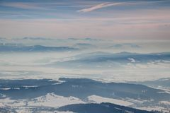 Winter scenery with foggy blue ridges and valleys in Slovakia. Frozen winter scenery with blue mountain ridges in the distance and snowy valleys filled with fog royalty free stock image