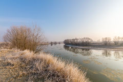 Winter scenery, with frozen river and frost cover vegetation on a cold, sunny, day Royalty Free Stock Photography