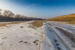 Winter scenery, with frozen river and ice covered sand dunes, on a cold sunny day Stock Photos