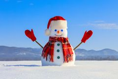 Winter scenery. Happy snowman in hat, red gloves and scarf on the background of mountains, blue sky. stock photography