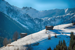 Winter scenery in the mountains with wooden hay huts Royalty Free Stock Images