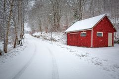 Winter scenery with red wooden house stock image
