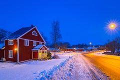 Winter scenery with red wooden house at night. In Sweden Royalty Free Stock Photos