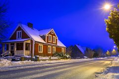 Winter scenery with red wooden house at night. In Sweden Stock Photography