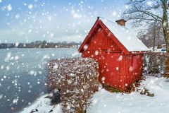 Winter scenery with red wooden house. Snowy winter scenery with red wooden house at the lake in Sweden Royalty Free Stock Image