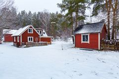 Winter scenery with red wooden house. In Sweden Royalty Free Stock Images
