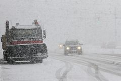 Winter Schneepflug säubert die Straße in der Stadt während eines enormen Schneesturmes, saubere Maschine des Schnees auf Boulevar Stockfotos
