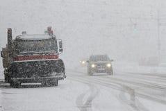 Winter Schneepflug säubert die Straße in der Stadt während eines enormen Schneesturmes, saubere Maschine des Schnees auf Boulevar Stockfotografie