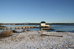 Winter by the sea. A thin layer of snow covers the shore. Two anglers are fishing by the bath-house. Oslofjorden, Norway stock photos